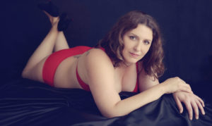 boudoir photo session with red lingerie laying on front