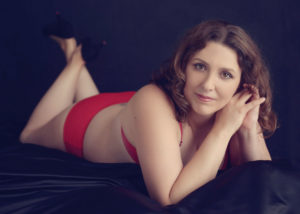 boudoir photo session with red bra and knickers and hands by face